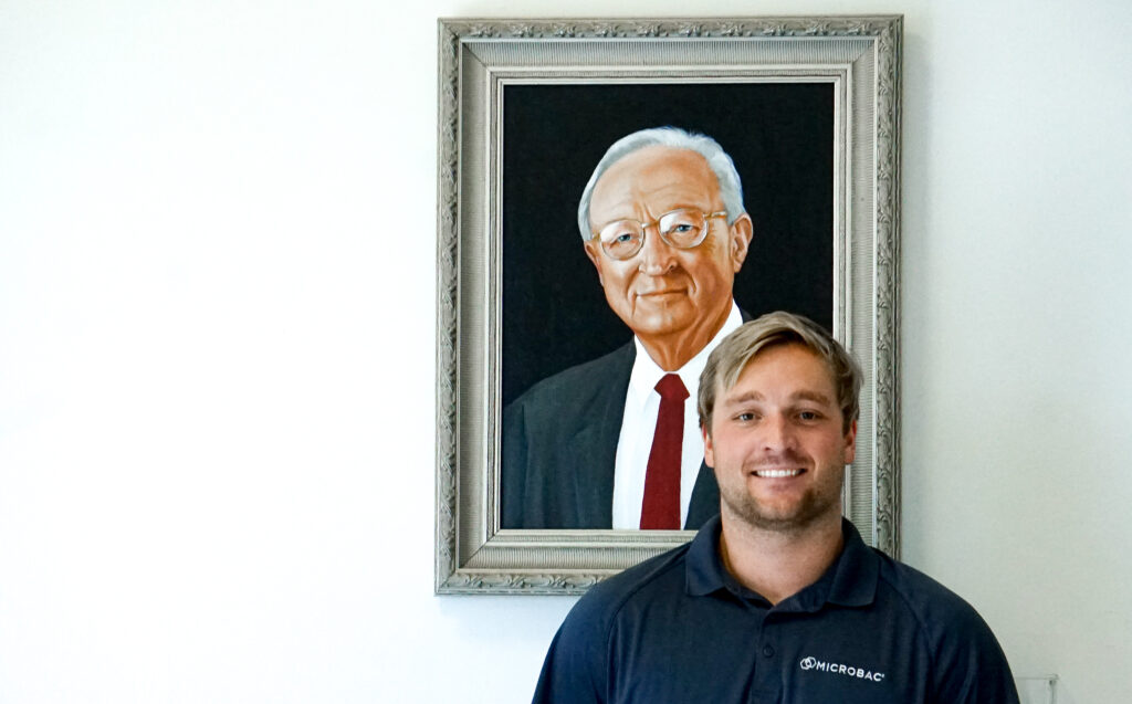 Family Owned Microbac Laboratories employee Grayson Boyce stands in front of painting of company founder Warne Boyce